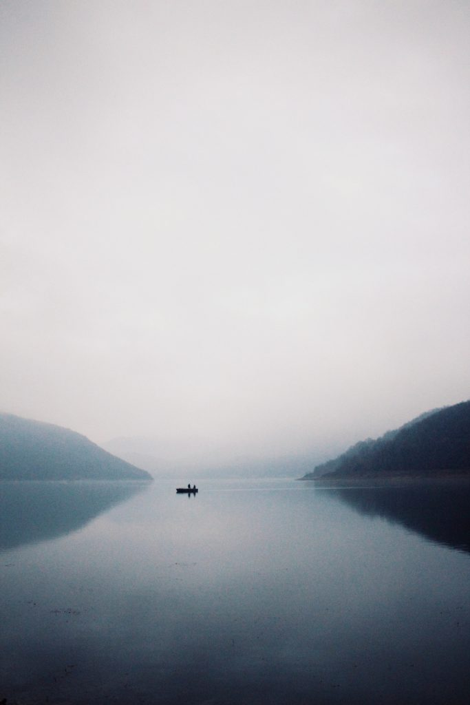 Fisher boat in the lake on a misty day