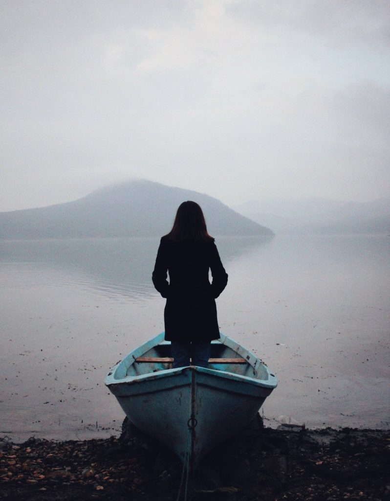 Portrait in a boat on a lake shore in a misty day